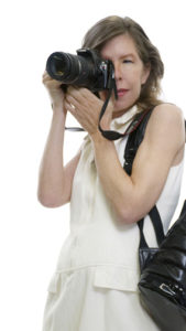 Woman wearing white holding camera to face with black backpack